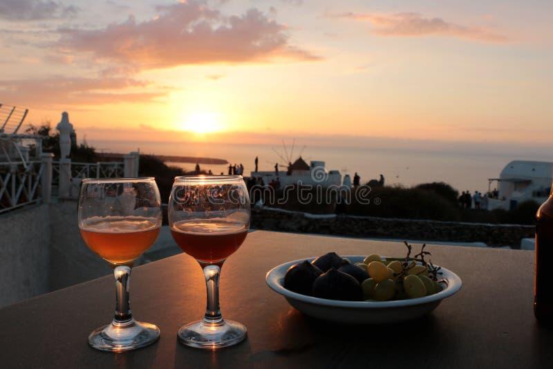 un verre de vin blanc et de fruits sur le balcon avec la vue de ville de caldeira au coucher du soleil photographie stock libre de droits