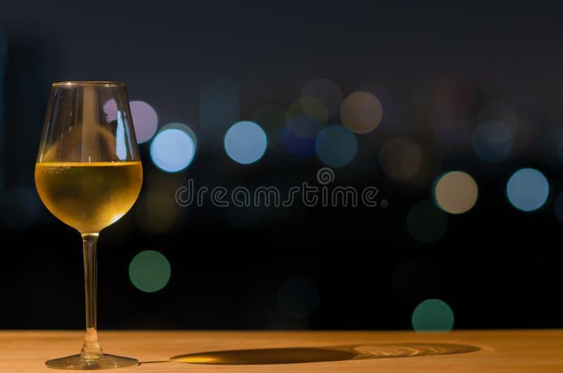 Un verre de vin blanc et de son ombre sur la table en bois de la barre de dessus de toit avec le bokeh coloré de la lumière et de photos libres de droits