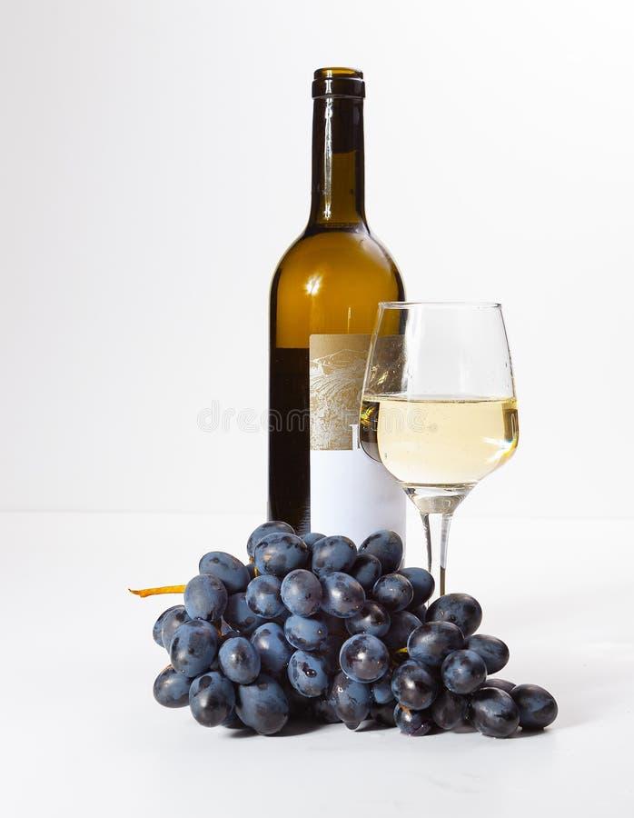 Un verre de vin blanc, un groupe de raisins, une bouteille ouverte image libre de droits