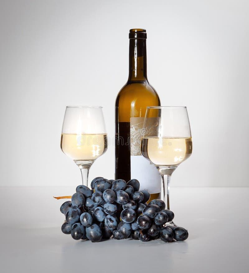 Un verre de vin blanc, un groupe de raisins, une bouteille ouverte photographie stock libre de droits