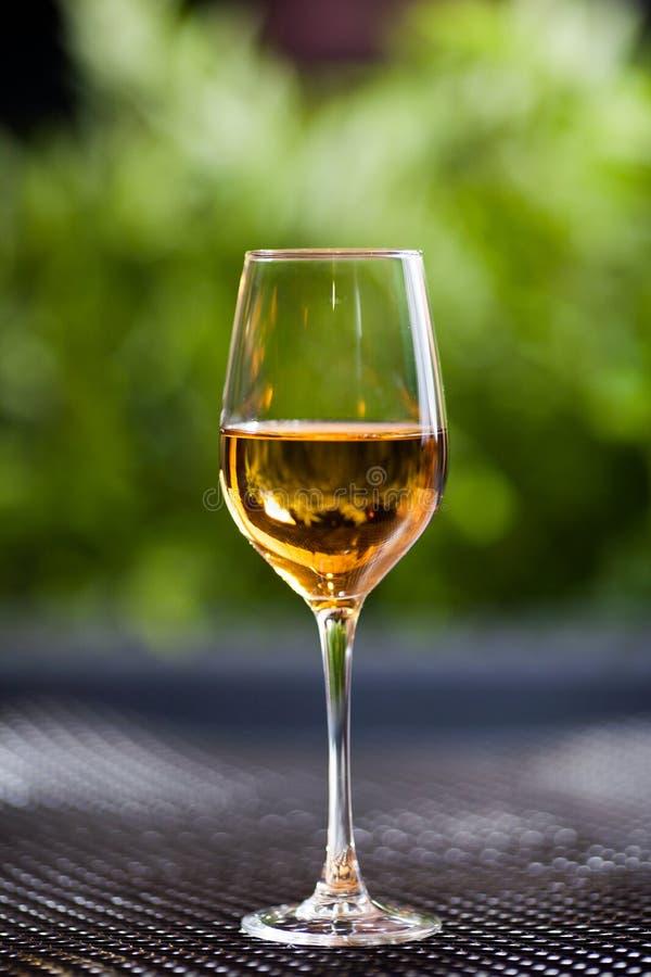 Un verre de vin blanc ou de jus de pomme se tient sur une table dans la bonne lumière avec un beau fond vert images stock