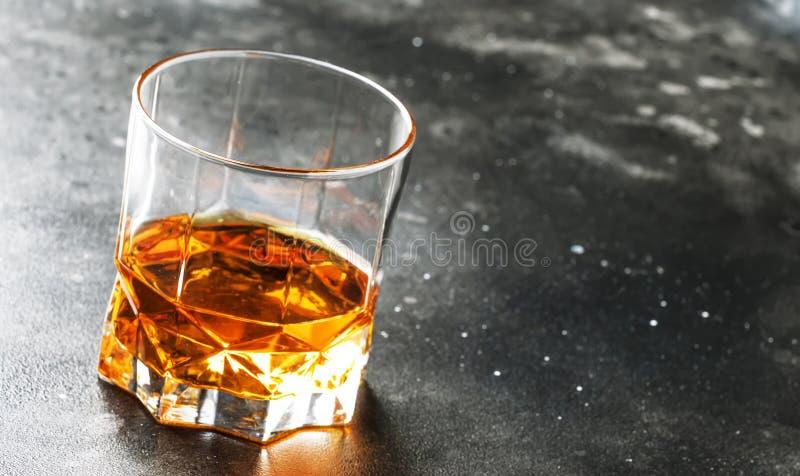 Un verre de whisky écossais d'or sur le vieux fond foncé de table de barre, foyer sélectif photos libres de droits