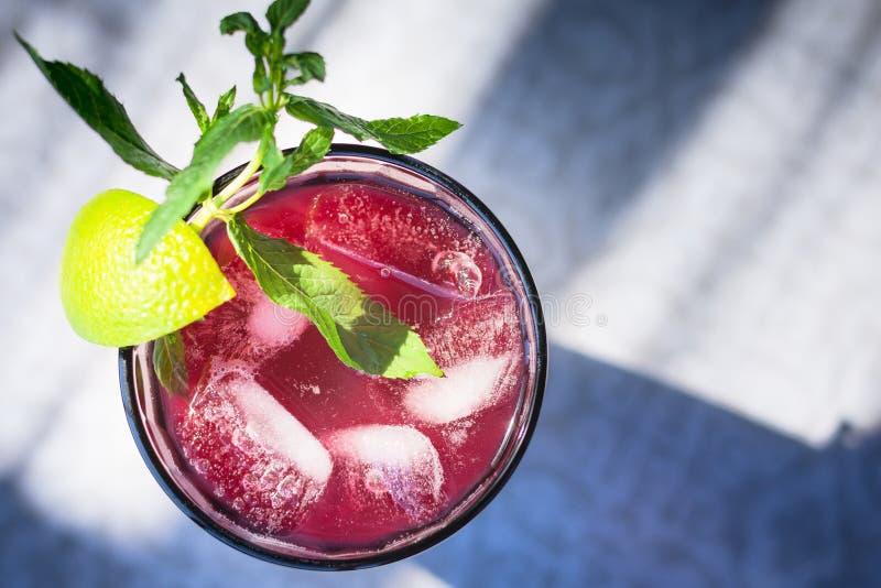 Un verre juteux frais avec une boisson de fruit et de baie, avec une tranche de chaux, un brin de menthe et des glaçons photographie stock