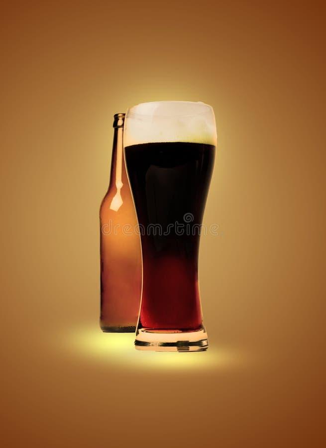 Un verre plein de la bière foncée et d'une bouteille vide derrière Traitement artistique photo stock