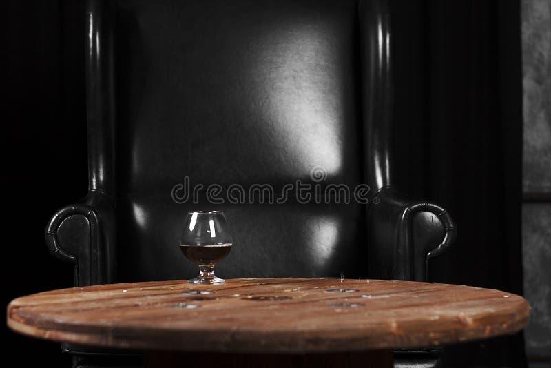 un verre pour le cognac sur une table en bois sur le fond d'une chaise en cuir images stock