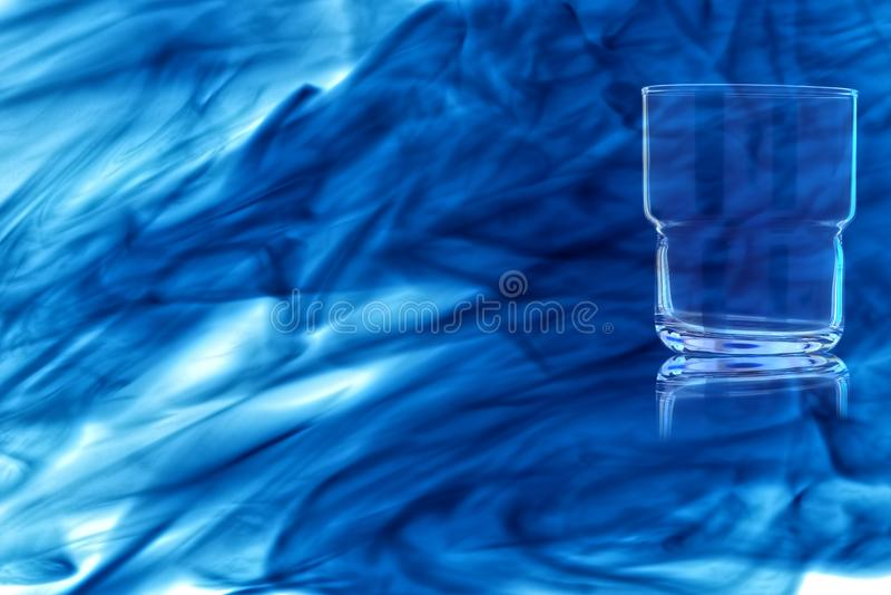 Un verre vide pour le whiskey enveloppé dans la fumée bleue photos libres de droits