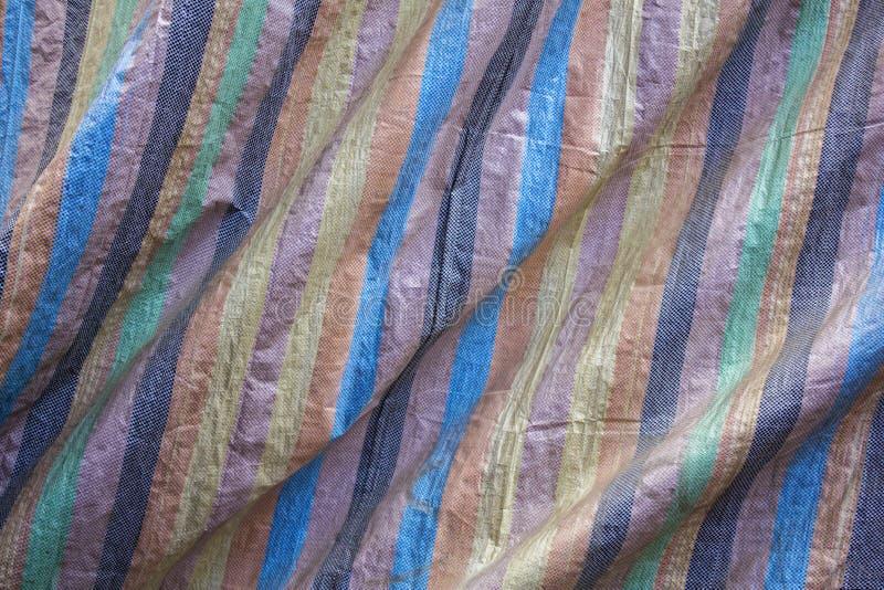 Un vert jaune noir brun bleu et des rayures roses sur le tissu rugueux avec des plis Texture de surface approximative le GR jaune photos stock
