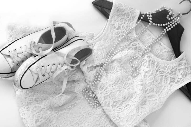 Un vestido blanco del cordón, un par de zapatillas de deporte en una suspensión de ropa de madera y un collar de la perla en blan foto de archivo libre de regalías
