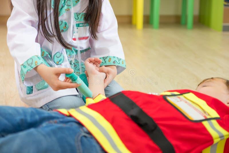 Un vestito da due bambini fino al vigile del fuoco e medico a rotolo giocano l'aula, Ki immagini stock