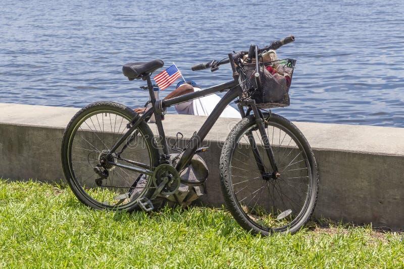 Un veterano pensionato parcheggia la sua bici accanto all'argine mentre scivola nelle acque basse dall'altro lato immagini stock libere da diritti