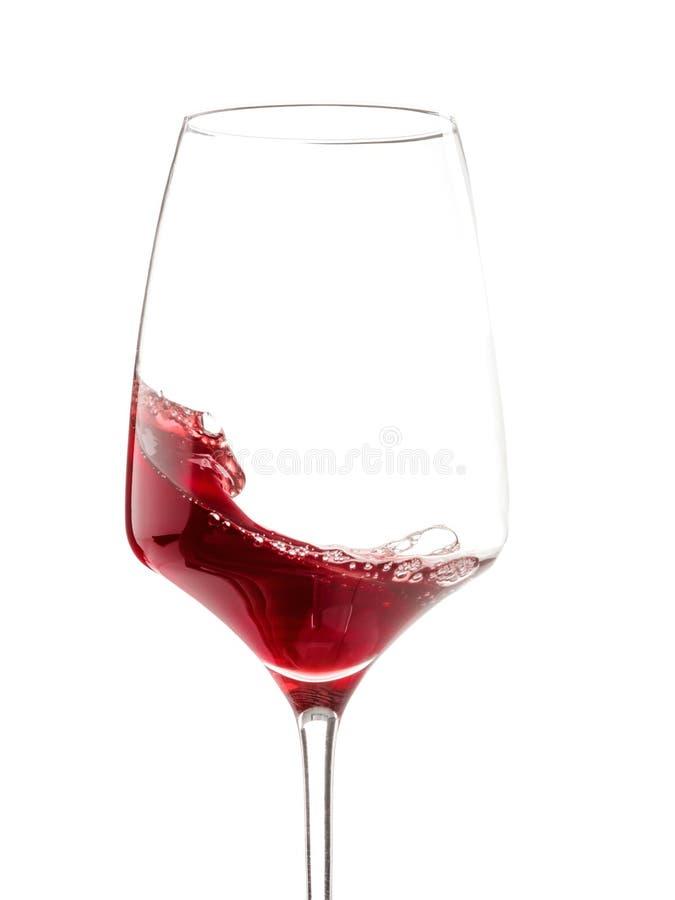 Un vetro con l'ondeggiamento del vino rosso Isolato su bianco Primo piano immagini stock libere da diritti