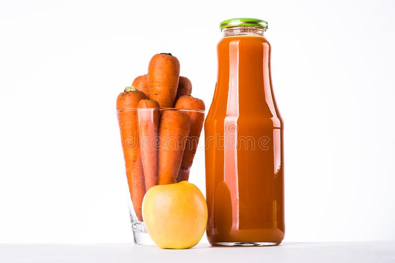 Un vetro con le carote un succo di carota e di mela in una bottiglia immagine stock