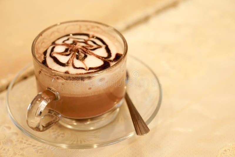 Un vetro del caffè caldo del latte con arte del cioccolato e della crema fotografie stock