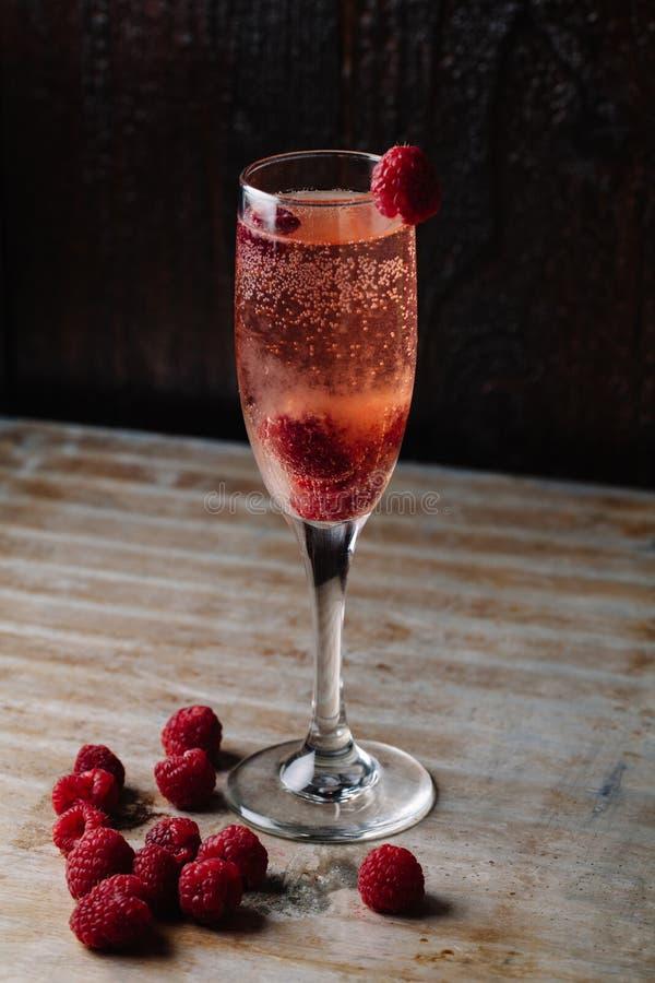 Un vetro del champagne del lampone su fondo rustico fotografie stock libere da diritti