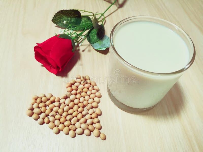 Un vetro del latte di soia, soia a forma di cuore, fiore rosa della decorazione, fondo di legno , fotografie stock libere da diritti