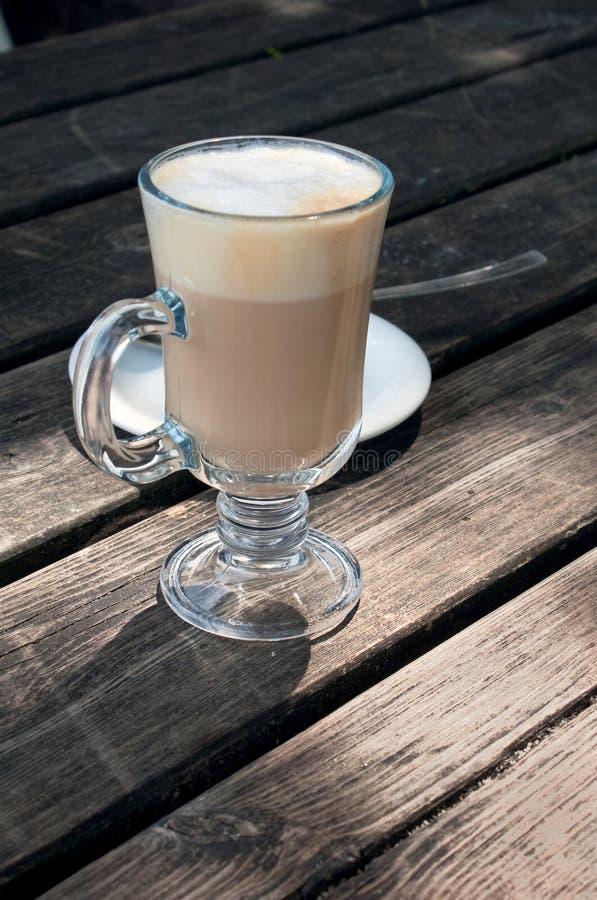 Un vetro del macchiato caldo del latte su una tabella di legno fotografia stock