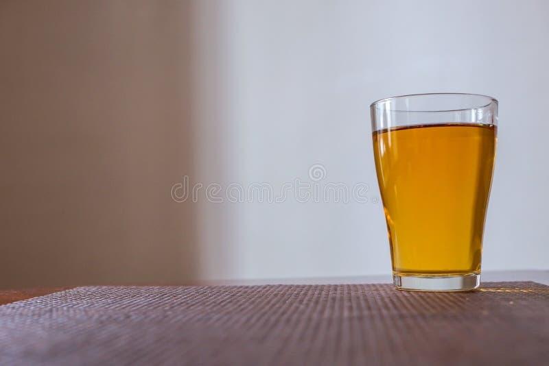 Un vetro del succo di mele è sulla tavola fotografie stock libere da diritti