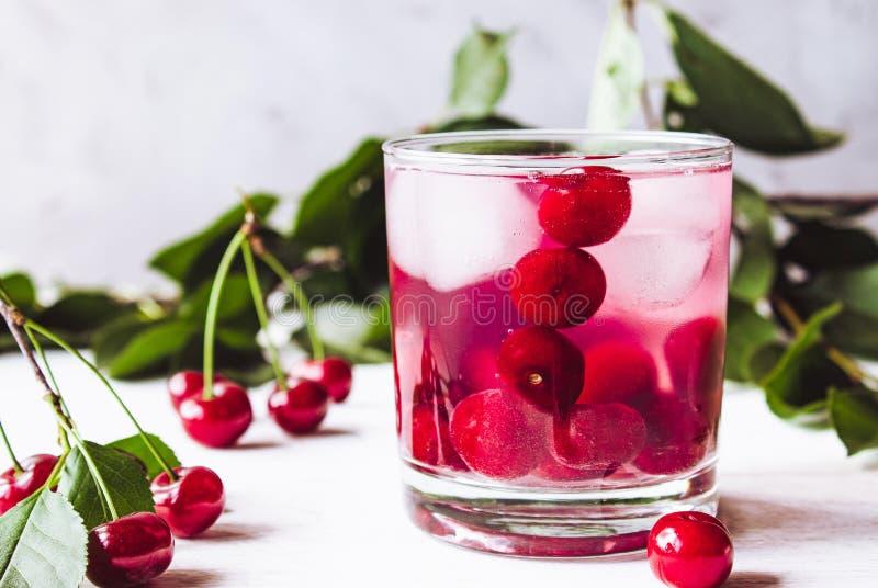 Un vetro della bevanda della ciliegia con ghiaccio in un vetro su un fondo di legno bianco Cocktail fresco di estate con le cilie fotografia stock libera da diritti