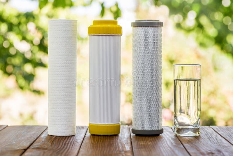 Un vetro delle cartucce purificate di filtro e dell'acqua sulla tavola di legno su sfondo naturale verde fotografie stock