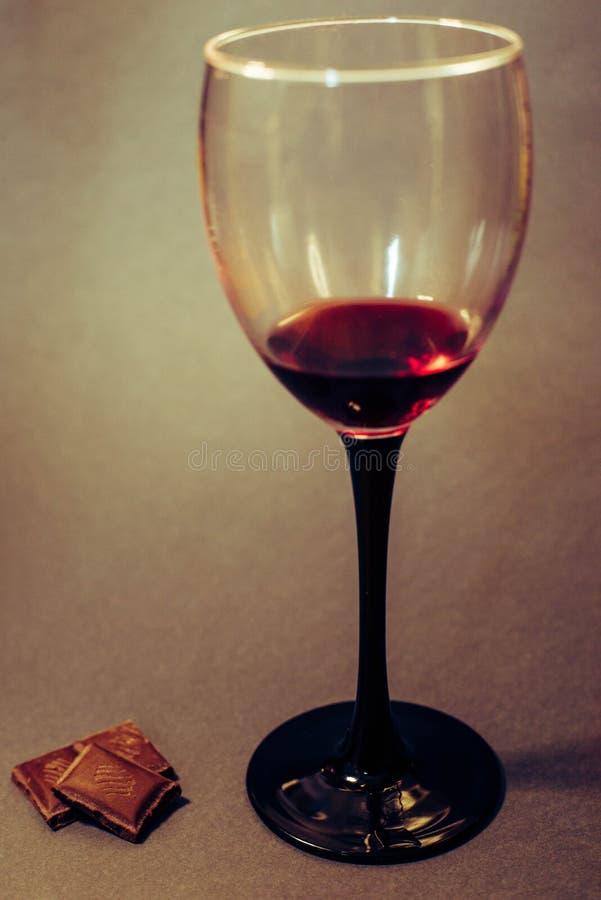 Un vetro delle fette del cioccolato e del vino rosso immagine stock libera da diritti