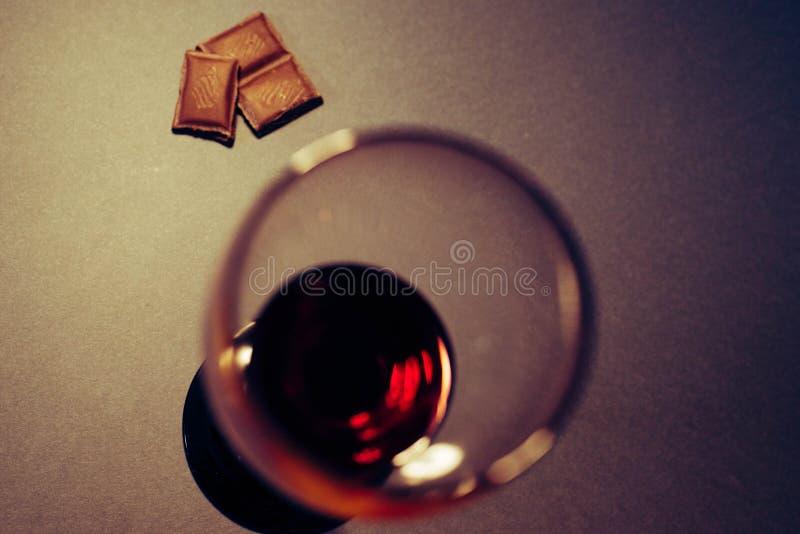 Un vetro delle fette del cioccolato e del vino rosso fotografia stock