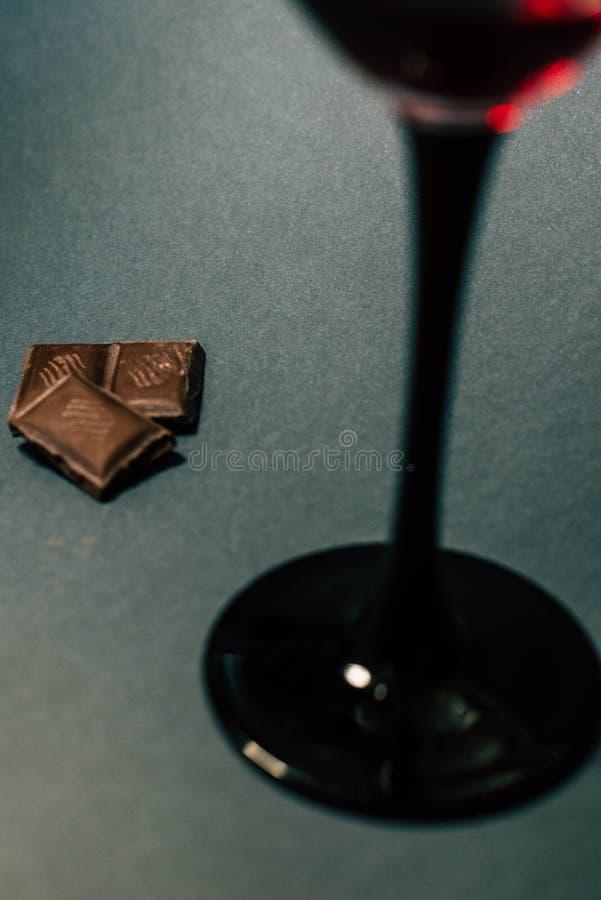 Un vetro delle fette del cioccolato e del vino rosso fotografie stock libere da diritti