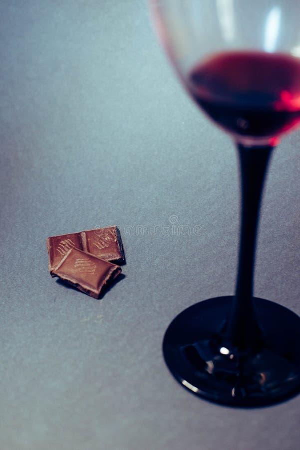 Un vetro delle fette del cioccolato e del vino rosso fotografia stock libera da diritti