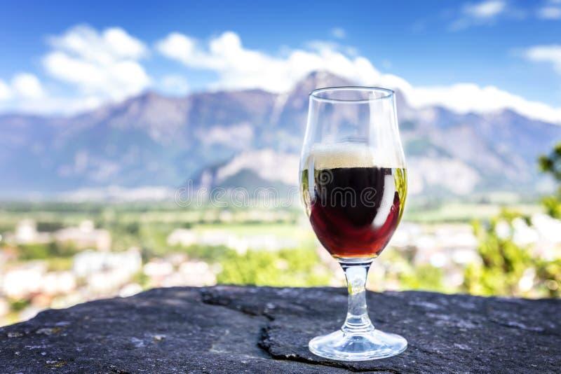 Un vetro di birra fresca sui precedenti delle montagne fotografia stock libera da diritti