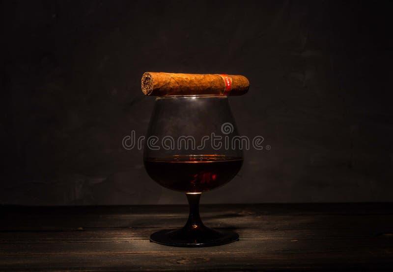 Un vetro di brandy con un sigaro cubano fotografia stock