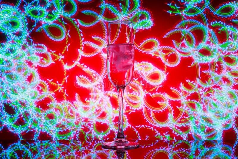 Un vetro di champagne con ghiaccio nei precedenti dei fuochi d'artificio fotografia stock libera da diritti