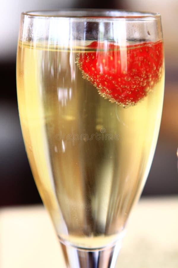 Un vetro di champagne con le fragole immagine stock