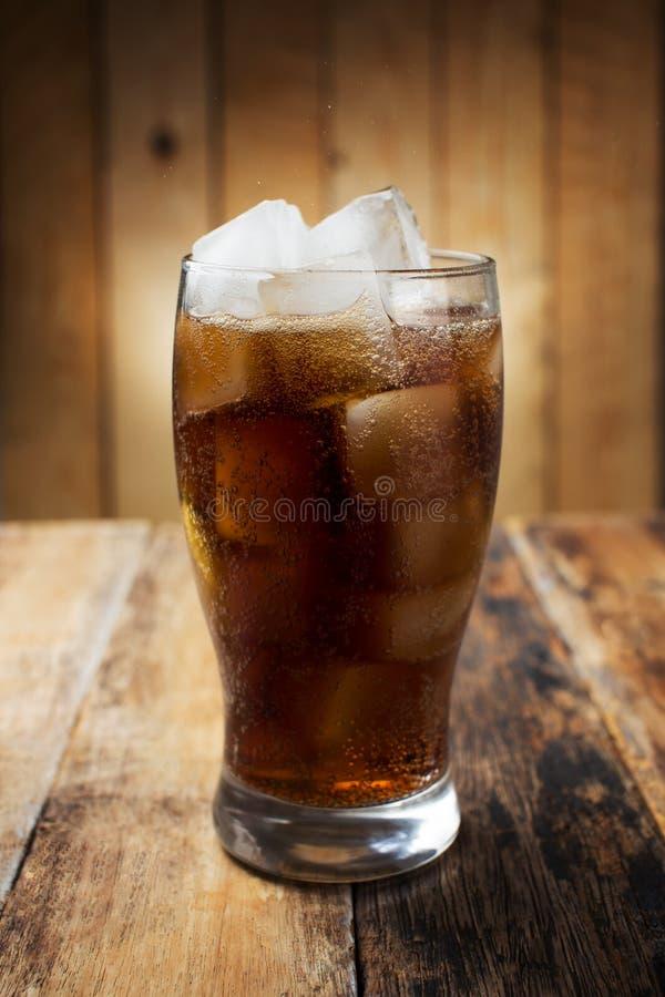 Un vetro di cola con i cubetti di ghiaccio immagini stock libere da diritti