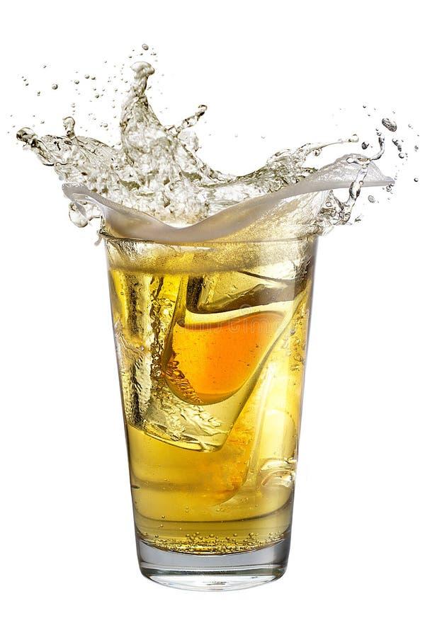 Un vetro di colpo ha riempito di alcool, disposto dentro un vetro con la birra Spruzzata immagine stock libera da diritti
