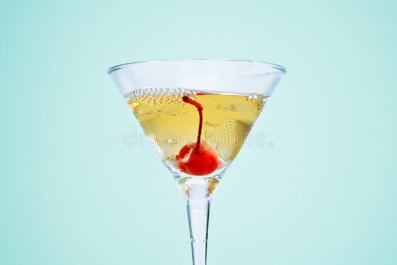Un vetro di martini, riempito di champagne con cherrie ed azoto liquido, creare vapore, isolato su fondo blu fotografia stock libera da diritti