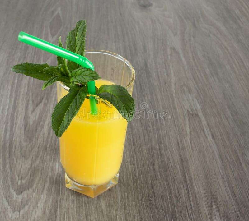 Un vetro di succo d'arancia con una paglia decorata con le foglie di menta immagini stock