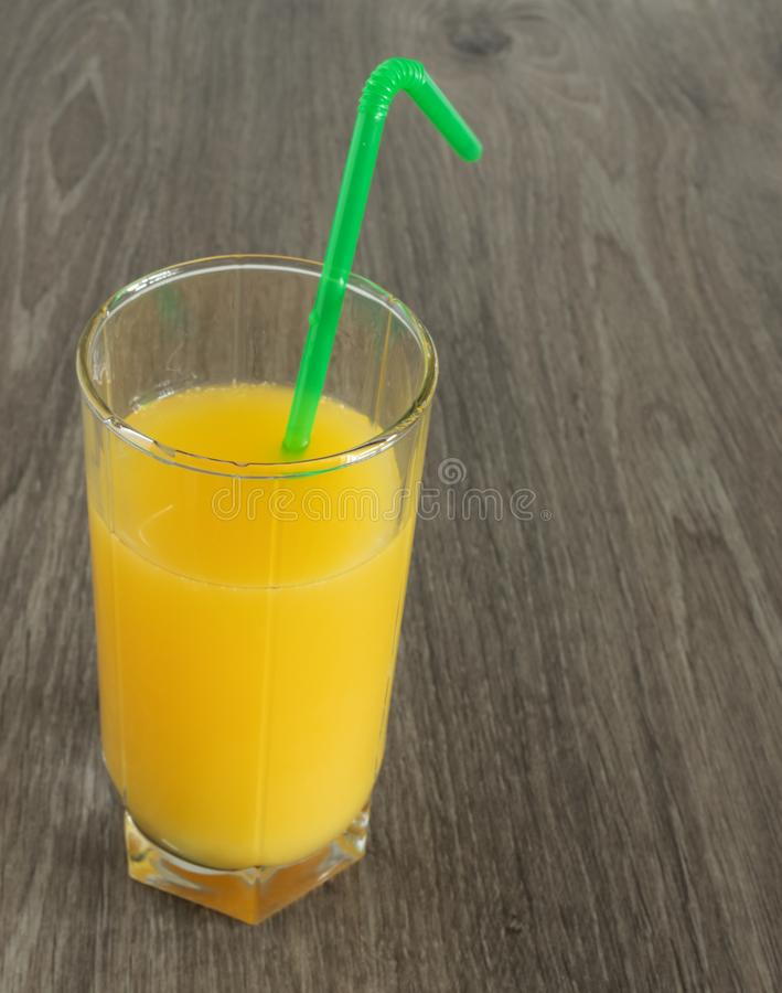 Un vetro di succo d'arancia con una paglia su un fondo di legno fotografia stock libera da diritti