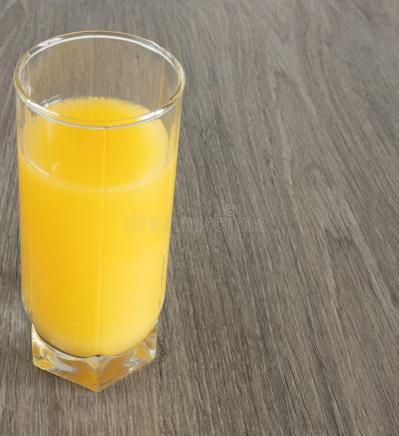Un vetro di succo d'arancia su una superficie legno-strutturata fotografie stock