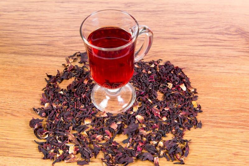 Un vetro di tè dai fiori dell'ibisco ed i sudanesi dei petali di rose sono sparsi su un primo piano della tavola immagine stock libera da diritti