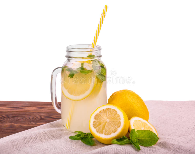 Un vetro di una paglia gialla e delle bevande mature con ghiaccio tritato e la menta su una tavola marrone, isolato su un fondo b immagini stock
