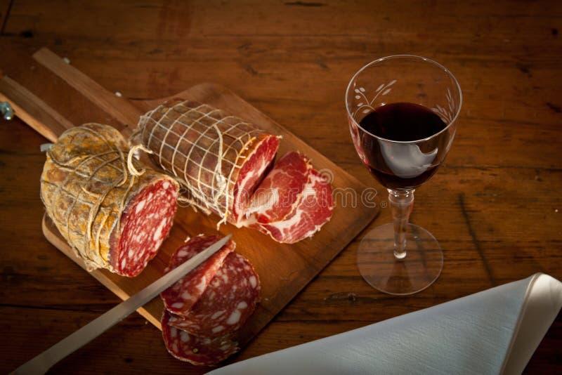 Un vetro di vino con salame da sopra fotografie stock libere da diritti