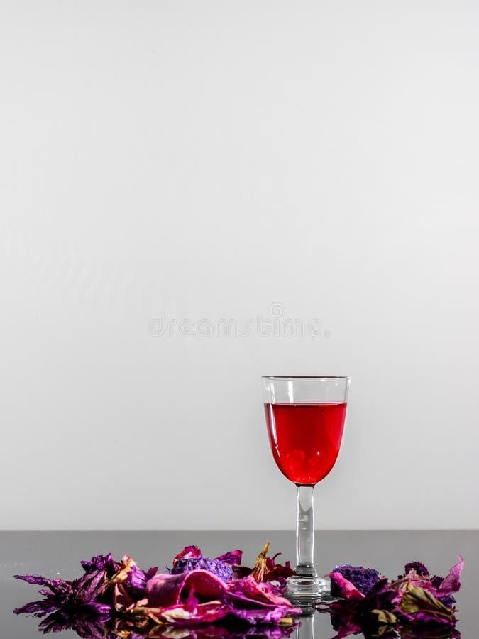 Un vetro di vino d'annata ed alcuni petali su una superficie riflettente immagine stock