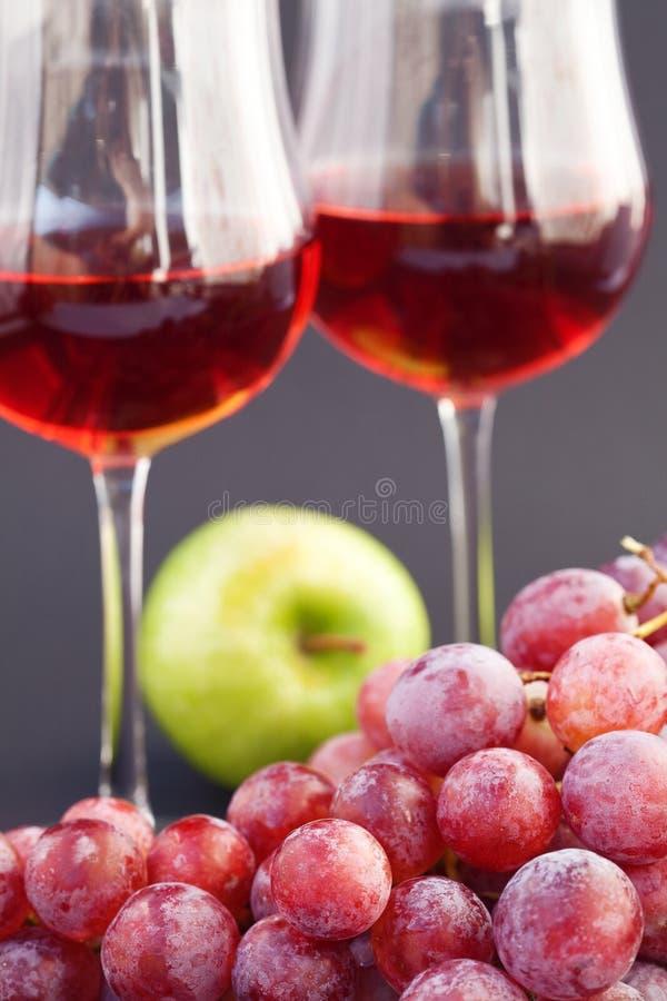 Un vetro di vino, della mela e dell'uva immagine stock libera da diritti
