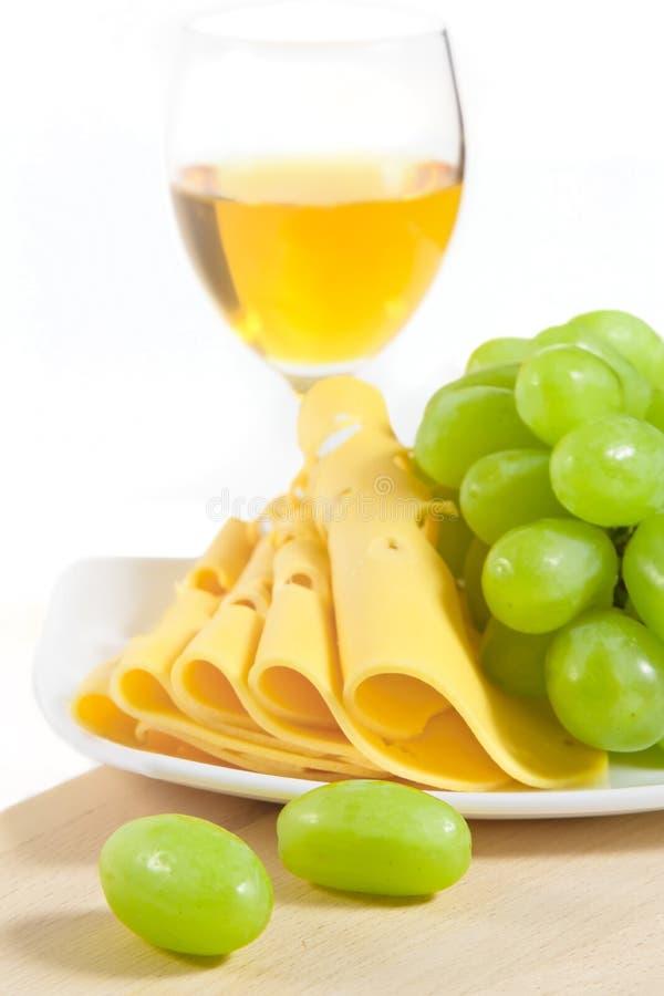 Un vetro di vino, di formaggio e dell'uva su legno fotografie stock