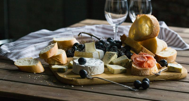 Un vetro di vino rosato è servito con le more e le baguette del piatto di formaggio Assortimento di formaggio con le bacche su fo immagini stock libere da diritti