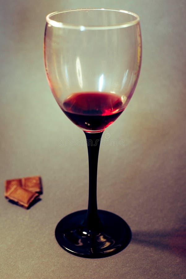 Un vetro di vino rosso con le fette del cioccolato immagini stock libere da diritti