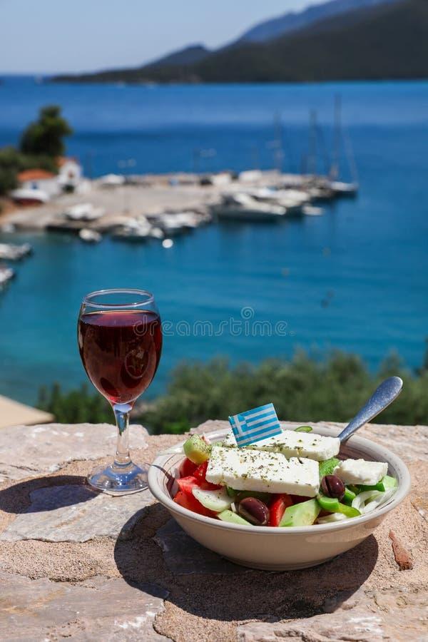 Un vetro di vino rosso e della ciotola di insalata greca con la bandiera greca sopra dalla vista del mare, concetto greco di fest fotografia stock libera da diritti