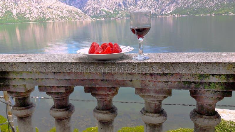 Un vetro di vino rosso e di un piatto delle fragole luminose sul balcone con le montagne nei precedenti fotografie stock