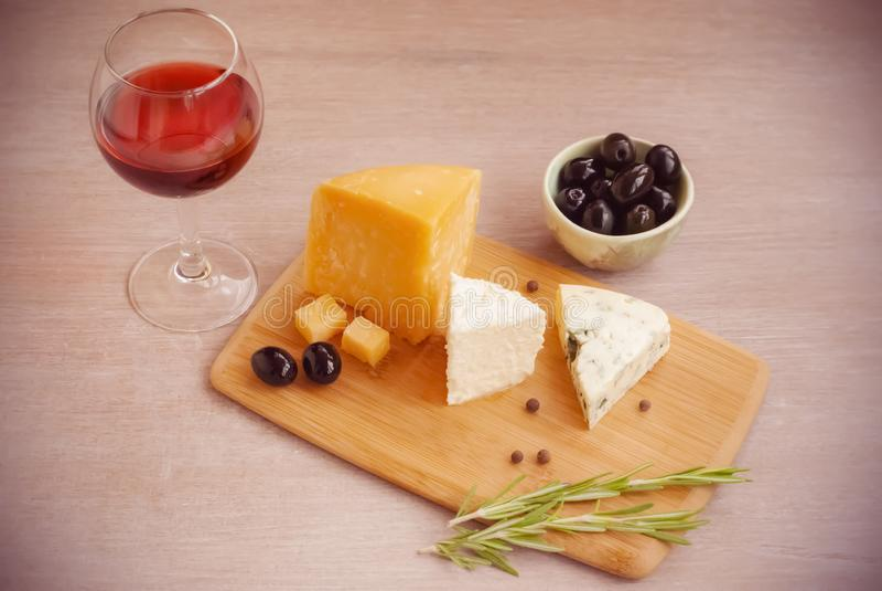 Un vetro di vino rosso, tipi differenti di formaggi, olive, un ramoscello dei rosmarini fotografie stock libere da diritti