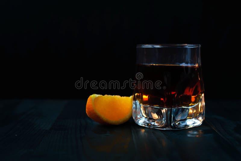 Un vetro di whiskey con una fetta arancio su un fondo nero e su una tavola di legno fotografie stock libere da diritti
