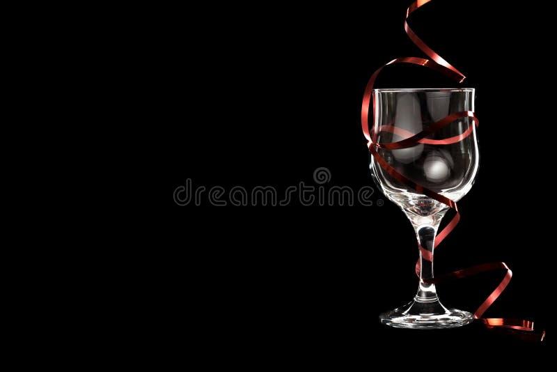 Un vetro vuoto di vino bianco con un nastro rosso fotografia stock libera da diritti